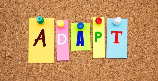 Kolorowe notatki z literami przypiętymi na tablicy. word adapt