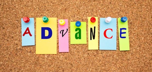 Kolorowe notatki z literami przypiętymi na tablicy. word advance.