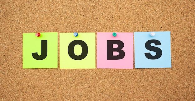 Kolorowe notatki z literami przypiętymi na tablicy. word jobs. miejsce do pracy.