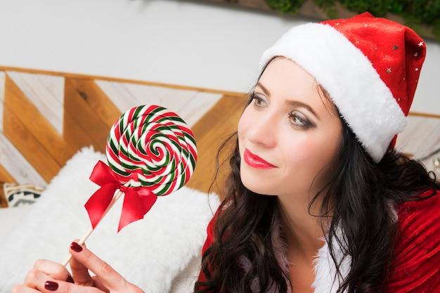 Kolorowe okrągłe cukierki do ssania. boże narodzenie nowy rok szczęśliwa kobieta w kapeluszu świętego mikołaja z lizakiem w rękach cukierków