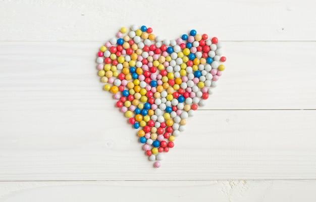 Kolorowe okrągłe cukierki leżące w kształcie serca na białym drewnianym tle