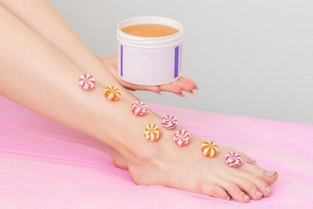 Kolorowe okrągłe cukierki na nodze kobiety, podczas gdy kobieta trzyma słoik z woskiem na tle z miejsca na kopię.