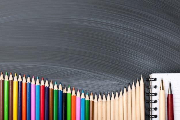 Kolorowe ołówki, długopisy i notatnik na tablicy