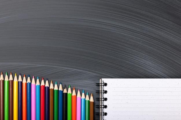 Kolorowe ołówki i notatnik na tablicy