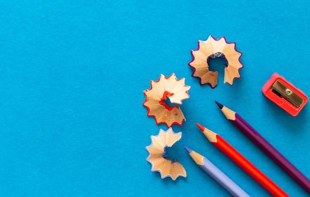 Kolorowe ołówki i wióry na niebieskim tle papieru. skopiuj miejsce