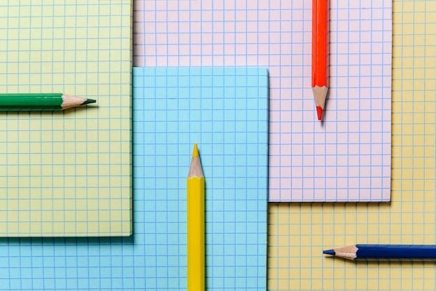 Kolorowe ołówki leżą na tle wielobarwnych arkuszy zeszytu.