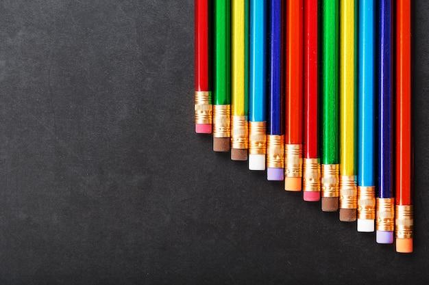 Kolorowe ołówki z gumkami w rzędzie na czarnym tle