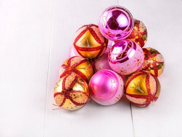 Kolorowe ozdoby świąteczne rozrzucone na białym drewnianym stole.