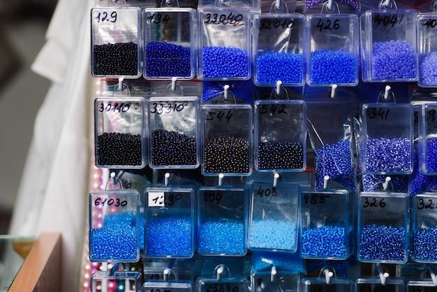 Kolorowe paczki szklanych koralików w plastikowych torebkach do pracy z koralikami w sklepie rzemieślniczym