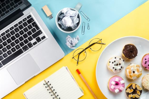 Kolorowe pączki w połączeniu z laptopami i przedmiotami w biurze