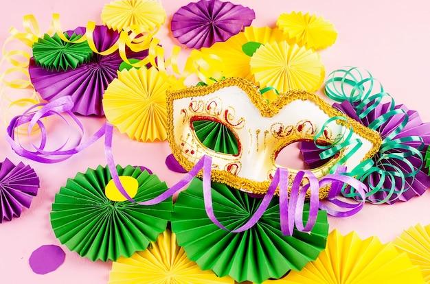 Kolorowe papierowe konfetti, karnawałowa maska i kolorowa serpentyna na różowym tle
