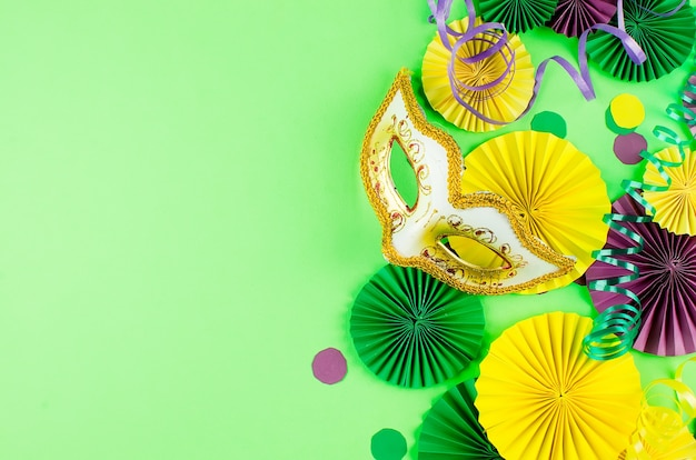 Kolorowe papierowe konfetti, karnawałowa maska i kolorowa serpentyna na zielonym tle