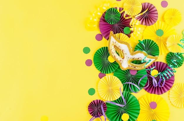 Kolorowe papierowe konfetti, karnawałowa maska i kolorowa serpentyna na żółtym tle