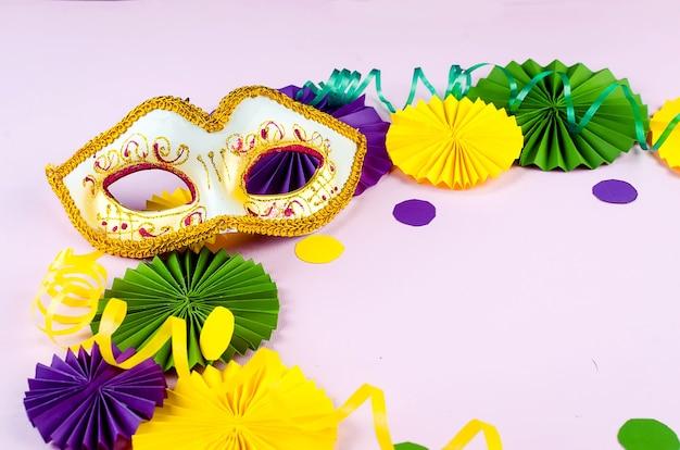 Kolorowe papierowe konfetti, maska karnawałowa i kolorowa serpentyna na różowym tle z kopią, kartką okolicznościową i szablonem zaproszenia na przyjęcie na karnawał lub urodziny, mardi gras,