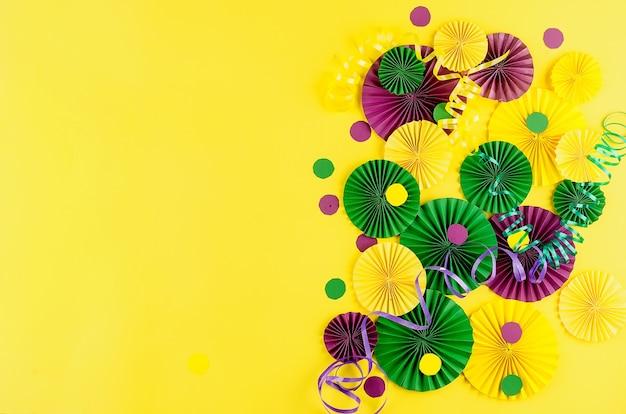 Kolorowe papierowe konfetti, maska karnawałowa i kolorowe serpentyny na żółtym tle z kopią, kartką z życzeniami i szablonem zaproszenia na przyjęcie na karnawał lub urodziny, mardi gras