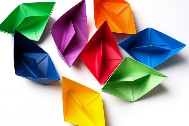 Kolorowe papierowe łodzie na jasnej białej powierzchni. skopiuj miejsce