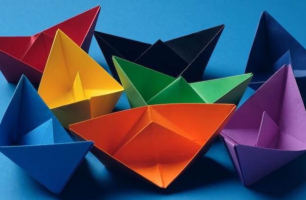Kolorowe papierowe łodzie na jasnej niebieskiej powierzchni. skopiuj miejsce