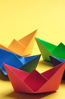 Kolorowe papierowe łodzie na jasnej żółtej powierzchni. skopiuj miejsce