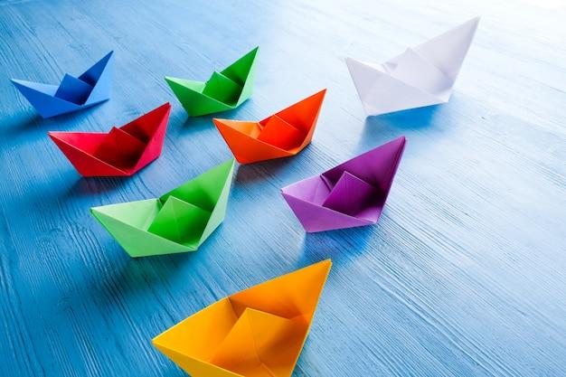 Kolorowe papierowe łodzie na niebieskim stole