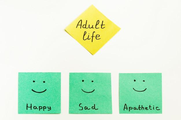"""Kolorowe papierowe notatki z napisami """"dorosłe życie"""", """"szczęśliwe"""", """"smutne"""", """"apatyczne"""" na białym tle."""