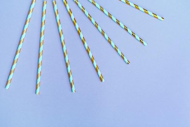Kolorowe papierowe słomki koktajlowe ze złotym wzorem w paski na urodziny lub wakacje. widok kreatywny uroczystości.