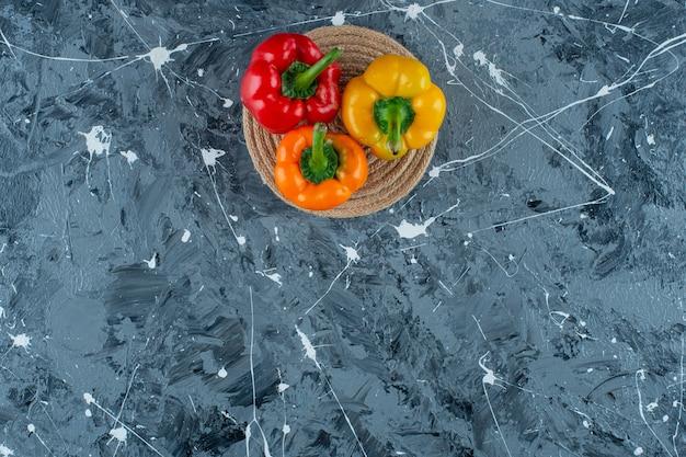 Kolorowe papryki na trójnogu, na marmurowym tle.