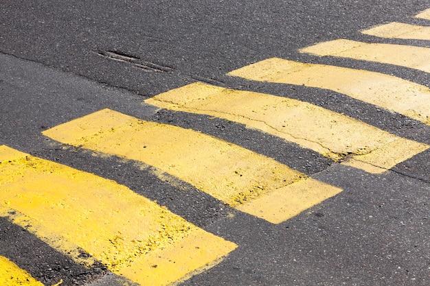 Kolorowe paski sztuczne nierówności na drodze do obserwacji prędkości samochodów, zbliżenie starych oznaczeń drogowych