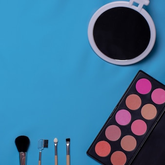 Kolorowe pędzle kosmetyczne, cienie do powiek, lusterko na niebieskim tle. zestaw do makijażu. płaska świecka, kopia przestrzeń, tło dla projektu
