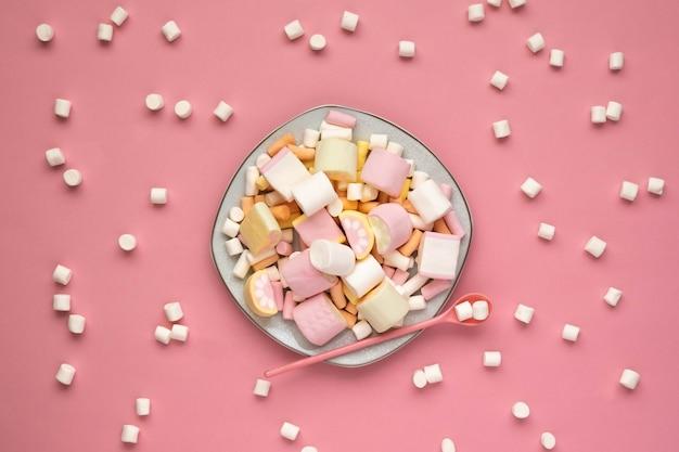 Kolorowe pianki na białym kwadratowym talerzu na białym tle na różowym tle. rozproszone pianki. zbliżenie tekstury puszystego prawoślazu. płaskie ułożenie