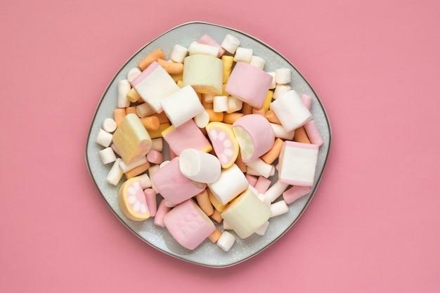 Kolorowe pianki na białym kwadratowym talerzu na białym tle na różowym tle. zbliżenie tekstury puszystego prawoślazu.