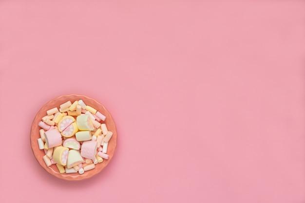 Kolorowe pianki na różowym naczyniu na białym tle na różowym tle. puszysty zbliżenie tekstury marshmallow. płaskie ułożenie