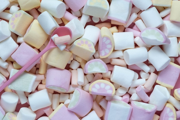Kolorowe pianki na różowym naczyniu na białym tle na różowym tle. puszysty zbliżenie tekstury marshmallow.