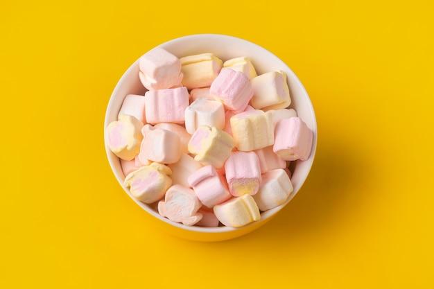 Kolorowe pianki w talerzu na żółtym tle