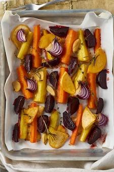Kolorowe pieczone warzywa na tacy z pergaminem. mieszanka marchwi, buraków, rzepy, rutabaga