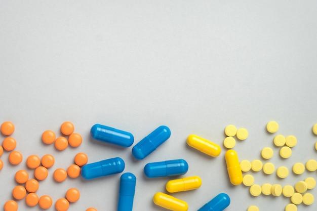 Kolorowe pigułki i kapsułki, lek na szarym tle z miejsca kopiowania. pojęcie zdrowia i leków. widok z góry.