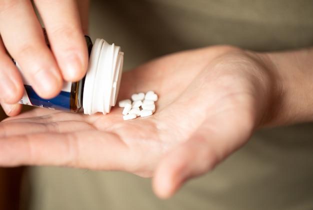 Kolorowe pigułki i leki w dłoni