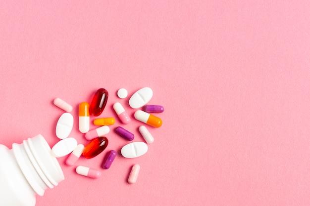 Kolorowe pigułki na różowym tle