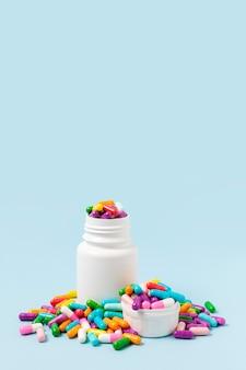 Kolorowe pigułki w białej butelce