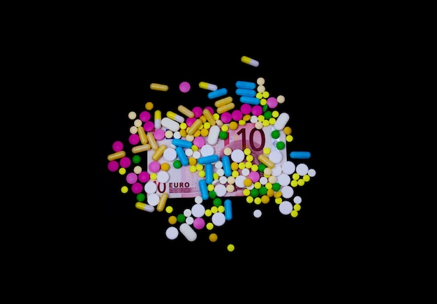 Kolorowe pigułki z pieniędzmi na ciemnym tle
