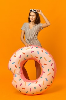 Kolorowe pionowe zdjęcie uroczej przyjaznej dwudziestoletniej kobiety w ładnej sukience