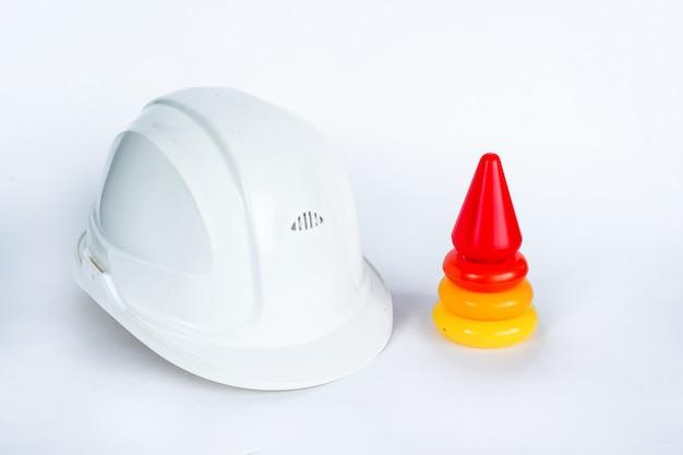 Kolorowe piramidy dla dzieci i biały hełm inżyniera budownictwa na białym tle