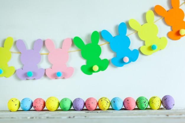 Kolorowe pisanki i ręcznie robiona girlanda wielkanocna króliczka na beżowym tle. koncepcja wesołych świąt.