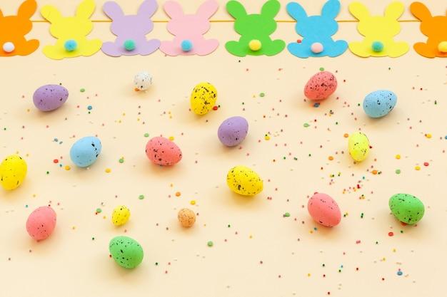 Kolorowe pisanki i ręcznie robiona girlanda wielkanocna króliczka na beżowym tle. widok z góry, płaski układ. koncepcja wesołych świąt.