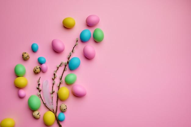 Kolorowe pisanki i wierzba na różowym tle, widok z góry