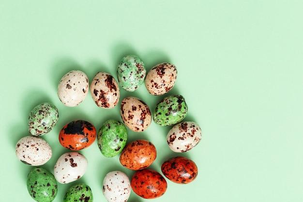 Kolorowe pisanki przepiórcze na jasnozielonym. wiosenna kompozycja wielkanocna z cukierkami czekoladowymi.