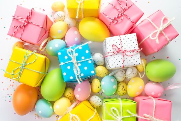 Kolorowe pisanki, pudełka z prezentami są na jasnym tle.