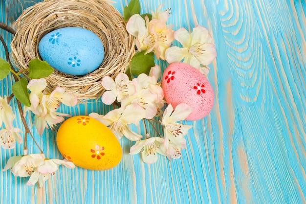 Kolorowe pisanki w gniazdo słomy i gałąź z kwiatami na niebieskim tle drewnianych