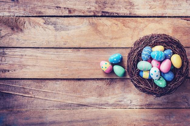 Kolorowe pisanki w gnieździe na tle drewna z miejsca