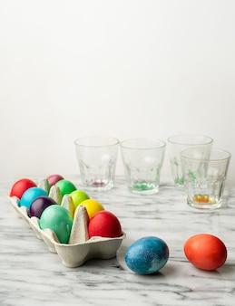 Kolorowe pisanki w kartonowym pudełku na kuchennym blacie, szklanki z resztkami barwnika