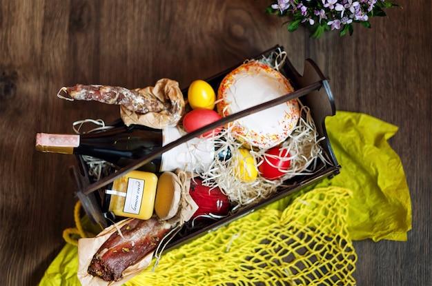 Kolorowe pisanki w koszu z ciastem, czerwonym winem, hamonem lub suszonym kiełbasą